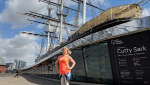 Marathon runner wearing an orange top in front of Cutty Sark